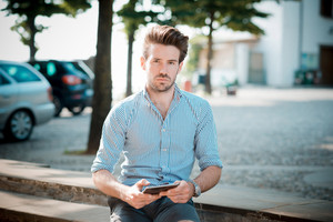 young handsome hipster modern man outdoor using tablet in summertime