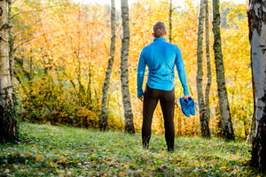 Young handsome hipster runner in blue sweatshirt holding pair of sports shoes outside in colorful sunny autumn nature. Rear view
