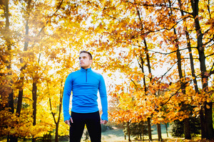 Young handsome hipster runner in blue sweatshirt outside in colorful sunny autumn nature