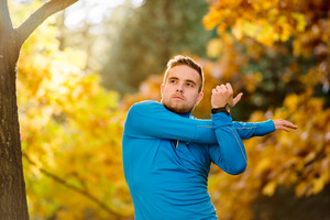 Young handsome hipster runner stretching arm outside in sunny autumn nature