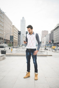 Young handsome indian contemporary business man walking through the city using smarpthone looking downward the screen-  technology, network, business, finance concepts