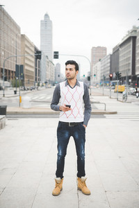Young handsome indian contemporary business man walking through the city using smarpthone overlooking-  technology, network, business, finance concepts