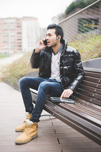 Young handsome indian contemporary businessman seated on a bench in a park using tablet talking smartphone with one earphone already on - business, work, study, technology concept