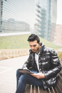 Young handsome indian contemporary businessman seated on a bench in a park using tablet while listening music with earphones looking downward on the screen  - business, work, study, technology concept