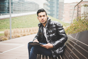 Young handsome indian contemporary businessman seated on a bench in a park using tablet while listening music with earphones overlooking left  - business, work, study, technology concept