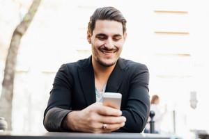 Young handsome italian boy seated on a bar in the city center using a smartphone, looking downward the screen, smiling - social network, communication, technology concept