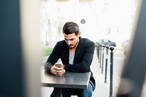 Young handsome italian boy seated on a bar in the city center using a smartphone - social network, communication, technology concept