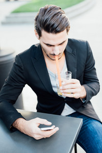 Young handsome italian boy seated on a bar in the city drinking a juice while chechking his smartphone - relax, technology, social network concept