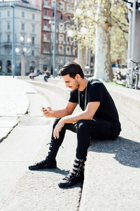 Young handsome italian boy seated on a sidewalk using a smartphone connected online - social network, technology concept