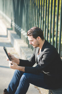 Young handsome italian boy seated on a sidewalk using a tablet connected online - technology, social network concept