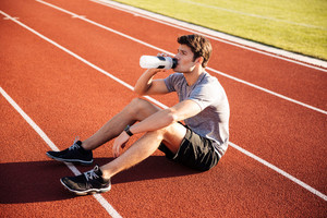 Young handsome man athlete resting at the stadium and drinking water