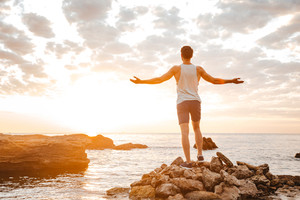 Young handsome man athlete standing backwards with arms raised at the rocky beach by the sea looking at sunset