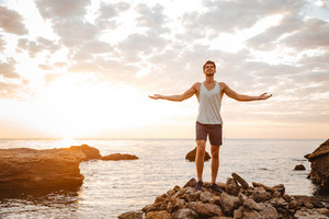 Young handsome man athlete standing with arms raised at the rocky beach by the sea looking at sunset