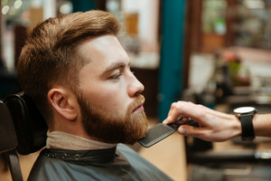 Young handsome man getting beard haircut by hairdresser while sitting in chair at barbershop.