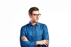 Young handsome man in blue denim shirt and black eyeglasses, arms crossed. Studio shot on white background, isolated.