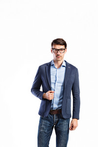 Young handsome man in blue shirt, jacket and black eyeglasses. Studio shot on white background, isolated.