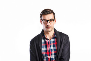 Young handsome man in checked red and blue shirt, gray sweater and black eyeglasses. Studio shot on white background, isolated.