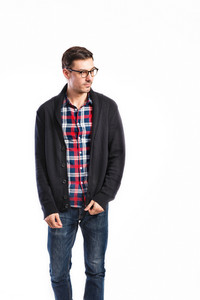 Young handsome man in checked red and blue shirt, gray sweater, jeans and black eyeglasses, hands in pockets. Studio shot on white background, isolated.