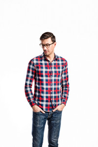 Young handsome man in checked red and blue shirt, jeans and black eyeglasses, hands in pockets. Studio shot on white background, isolated.