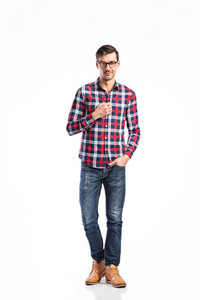 Young handsome man in checked red and blue shirt, jeans and black eyeglasses. Studio shot on white background, isolated.