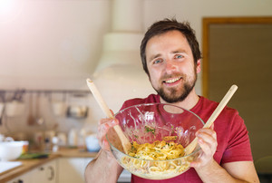 Young handsome man in the kitchen holding a bowl with salmon tagliatelle