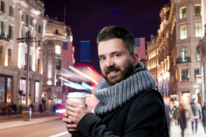 Young handsome man in winter clothes holding a coffee cup in illuminated night London city
