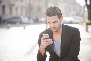Young handsome man seated on a sidewalk using a smart phone connected online - social network, technology concept