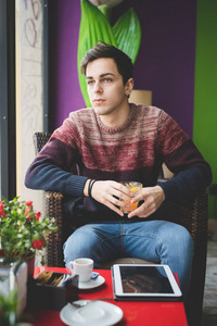 young handsome man sitting at the bar holding orange juice glass
