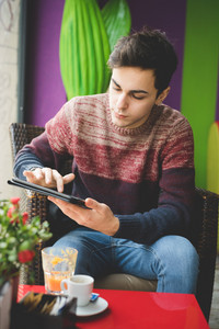 young handsome man sitting at the bar using tablet connected wireless online