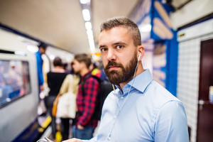 Young handsome man standing on subway platform