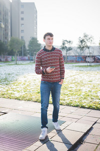 young handsome man using smartphone in the city