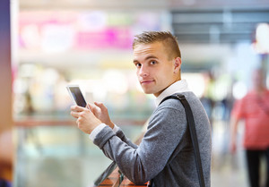 Young handsome man using tablet in shopping centre