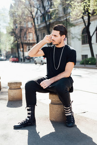 Young handsome millennial man seated on a sidewalk talking smart phone -