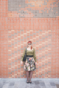 Young handsome redhead caucasian woman, leaning against a wall, looking in camera, smiling - pin up, carefreeness concept - wearing green shirt, floral skirt, bag and sunglasses