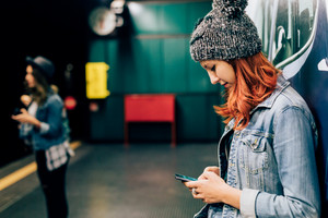young handsome redhead straight hair woman waiting in the underground for tube, one using smartphone - transport, technology concept