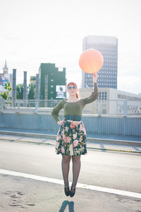 young handsome redhead woman jumping on the spot holding an orange balloon, hands on her hip, looking in camera smiling