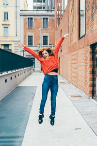 Young handsome redhead woman jumping outdoor in the city - girl power, satisfaction, goal concept