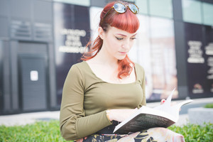 Young handsome redhead woman sitting on a small wall reading a book - culture, studying, relaxing concept
