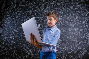 Young handsome school boy with notebook standing in front of big blackboard