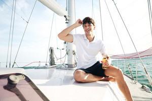 Young handsome smiling man in sunglasses drinking beer while sitting on the yacht