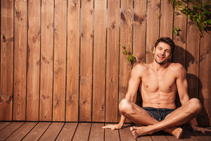 Young handsome smiling man in swimwear sitting with legs crossed over wooden background