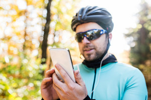 Young handsome sportsman riding his bicycle outside in sunny autumn nature. Holding smart phone, listening music.