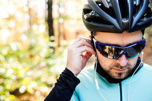 Young handsome sportsman riding his bicycle outside in sunny autumn nature, putting earphones into his ears, rear view