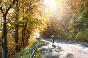Young handsome sportsman riding his bicycle outside in sunny autumn nature