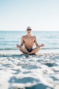young handsome sporty man doing yoga at the beach in summertime - relax, meditation, spiritually concept
