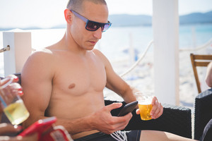 young handsome sporty man drinking beer and using smartphone at the beach bar in summertime - happy hour, relax concept