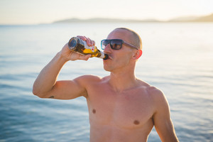 young handsome sporty man drinking beer at the beach sunset in summertime