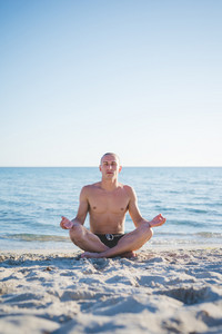 young handsome sporty man making yoga at the beach in summertime