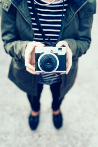Young handsome woman holding a vintage camera - photography, creative concept - focus on the camera