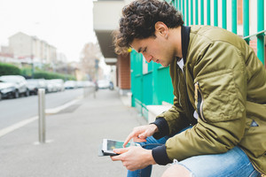 Young hansome caucasian man using a tablet, tapping the touchscreen - technology, social network, communication concept